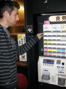 Buying a ramen lunch at the train station. You put your money in, choose what you want, and then present the printed ticket to the staff at the noodle bar. (But first, you find an English-speaking commuter to translate for you!)